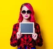 Νέο ρόδινο κορίτσι τρίχας στο κόκκινο πουκάμισο ταρτάν και πίνακας Στοκ Φωτογραφία