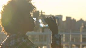 Νέο σγουρός-μαλλιαρό αφροαμερικανός πόσιμο νερό γυναικών στην οδό πόλεων, υγειονομική περίθαλψη απόθεμα βίντεο