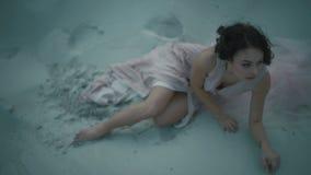 Νέο σεξουαλικό κορίτσι brunette στο ανοικτό ροζ φόρεμα που κλίνει στο έδαφος και σχετικά με το πρόσωπό της καθμένος στην αμμώδη α φιλμ μικρού μήκους