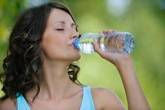 Νέο σκοτεινός-μαλλιαρό πόσιμο νερό γυναικών στοκ εικόνες