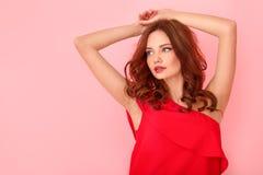 Νέο στούντιο γυναικών που απομονώνεται στο ροζ σε ένα κόκκινο φόρεμα που φαίνεται κατά μέρος θέτοντας στοκ φωτογραφίες με δικαίωμα ελεύθερης χρήσης