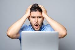 Νέο συγκλονισμένο άτομο στο μπλε πουκάμισο που χρησιμοποιεί το lap-top Στοκ Φωτογραφία