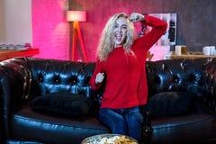 Νέο συναισθηματικό ελκυστικό watchi καναπέδων καναπέδων γυναικών μόνο στο σπίτι στοκ εικόνες