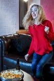 Νέο συναισθηματικό ελκυστικό watchi καναπέδων καναπέδων γυναικών μόνο στο σπίτι στοκ εικόνα