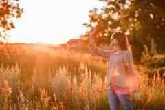 Νέο σύγχρονο κορίτσι στο ηλιοβασίλεμα υποβάθρου στοκ φωτογραφίες
