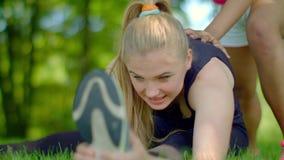 Νέο τέντωμα γυναικών υπαίθριο Τεντώνοντας άσκηση στο πάρκο απόθεμα βίντεο