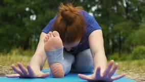 Νέο τέντωμα ποδιών άσκησης γυναικών στο πάρκο, που κάμπτει κάτω από το βλέμμα κεκλεισμένων των θυρών, υπαίθριος απόθεμα βίντεο