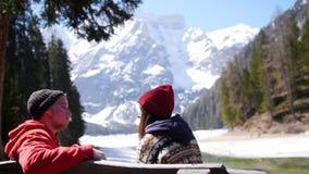 Νέο ταξίδι ζευγών Κάθισμα σε έναν πάγκο και απόλαυση της θέας απόθεμα βίντεο
