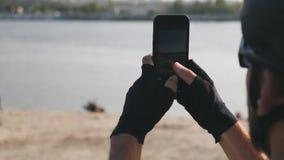 Νέο τηλέφωνο εκμετάλλευσης ποδηλατών στο χέρι του που παίρνει τις εικόνες του ποταμού και της πόλης που φορούν το κράνος, τα γυαλ απόθεμα βίντεο