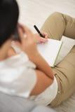Ομιλούν τηλέφωνο κυττάρων γυναικών και γράψιμο στο σημειωματάριο Στοκ Εικόνες