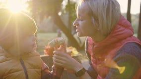 Νέο τσάι κατανάλωσης γυναικών και αγοριών στο πάρκο φθινοπώρου Τα κίτρινα φύλλα και πίνουν το τσάι στο πάρκο απόθεμα βίντεο