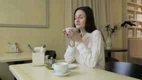 Νέο τσάι κατανάλωσης γυναικών σε έναν καφέ απόθεμα βίντεο