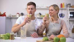 Νέο υγιές ζεύγος που πίνει το φρέσκο καταφερτζή, τις βιταμίνες και τα ανόργανα άλατα spirulina απόθεμα βίντεο