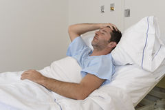 Νέο υπομονετικό άτομο που βρίσκονται στο νοσοκομειακό κρεβάτι που στηρίζεται κουρασμένο να φανεί λυπημένος και καταθλιπτικός που  Στοκ φωτογραφία με δικαίωμα ελεύθερης χρήσης