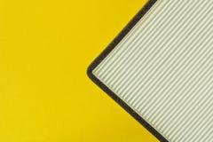 Νέο φίλτρο αέρα αυτοκινήτων στο κίτρινο υπόβαθρο κλείστε επάνω στοκ φωτογραφία με δικαίωμα ελεύθερης χρήσης