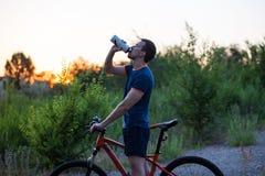 Νέο φίλαθλο άτομο που οδηγά ένα πόσιμο νερό ποδηλάτων από το αθλητικό μπουκάλι στο ηλιοβασίλεμα Στοκ φωτογραφία με δικαίωμα ελεύθερης χρήσης