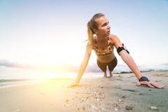 Νέο φίλαθλο κορίτσι που κάνει την άσκηση σανίδων στην παραλία στην ανατολή στοκ φωτογραφίες με δικαίωμα ελεύθερης χρήσης