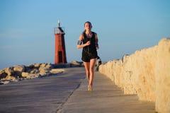 Νέο φίλαθλο κορίτσι που τρέχει μόνο στο όμορφο ηλιοβασίλεμα κοντά στο φάρο στοκ φωτογραφία με δικαίωμα ελεύθερης χρήσης