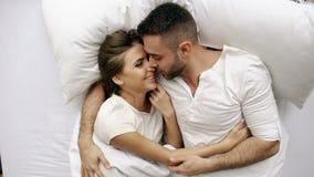 Νέο φιλί και αγκάλιασμα όμορφων και ζευγών αγάπης στο κρεβάτι ξυπνώντας το πρωί Τοπ άποψη του ελκυστικού ατόμου φιλμ μικρού μήκους