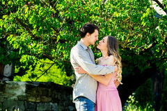 Νέο φιλώντας ζεύγος κάτω από το μεγάλο δέντρο με την ταλάντευση Στοκ Εικόνες