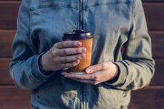 Νέο φλυτζάνι εκμετάλλευσης γυναικών του φρέσκου καφέ πρωινού ενάντια στο ξύλινο πρόσωπο ανθρώπων ελεύθερου χρόνου ελεύθερου χρόνο στοκ φωτογραφία