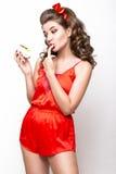 Νέο φρέσκο κορίτσι στις κόκκινες πυτζάμες μεταξιού, το χαμόγελο και το αναδρομικό καρφίτσα-επάνω ύφος μπουκλών Πρόσωπο ομορφιάς,  Στοκ φωτογραφία με δικαίωμα ελεύθερης χρήσης