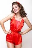 Νέο φρέσκο κορίτσι στις κόκκινες πυτζάμες μεταξιού, το χαμόγελο και το αναδρομικό καρφίτσα-επάνω ύφος μπουκλών Πρόσωπο ομορφιάς,  Στοκ Φωτογραφίες