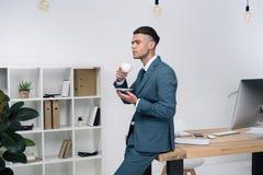 Νέο φλιτζάνι του καφέ εκμετάλλευσης επιχειρηματιών καθμένος στον πίνακα γραφείων και κοιτάζοντας μακριά Στοκ Εικόνες