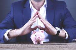 Νέο χέρι επιχειρησιακών ατόμων που κρατά τη piggy τράπεζα στοκ φωτογραφία