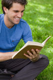 Νέο χαμογελώντας άτομο που διαβάζει ένα βιβλίο εγκαθιστώντας στη χλόη Στοκ Εικόνα