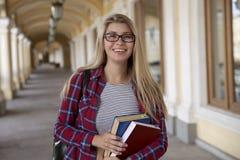 Νέο χαμογελώντας κορίτσι σπουδαστών με τη διαθέσιμη τοποθέτηση βιβλίων για ένα portr στοκ εικόνα με δικαίωμα ελεύθερης χρήσης