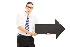 Νέο χαμογελώντας άτομο με τα γυαλιά που κρατά ένα μεγάλες βέλος και μια υπόδειξη Στοκ φωτογραφίες με δικαίωμα ελεύθερης χρήσης