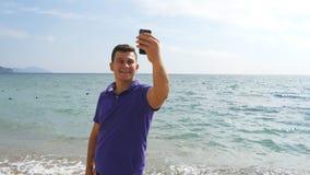 Νέο χαμογελώντας άτομο που έχει μια τηλεοπτική κλήση στο έξυπνο τηλέφωνο στην παραλία θάλασσας Ευτυχής τύπος που κάνει τις τηλεοπ απόθεμα βίντεο