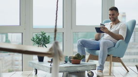 Νέο χαμογελώντας άτομο που κάνει on-line να ψωνίσει χρησιμοποιώντας την ψηφιακή συνεδρίαση υπολογιστών ταμπλετών στο μπαλκόνι στο απόθεμα βίντεο