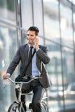 Νέο χαμογελώντας επιχειρησιακό άτομο με το τηλέφωνο που οδηγά ένα ποδήλατο Στοκ φωτογραφία με δικαίωμα ελεύθερης χρήσης