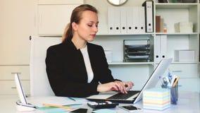 Νέο χαμογελώντας θηλυκό που εργάζεται στο γραφείο στο lap-top φιλμ μικρού μήκους