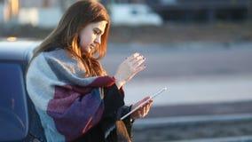 Νέο χαμογελώντας κορίτσι με το μαντίλι που χρησιμοποιεί τον υπολογιστή ταμπλετών υπαίθρια στη συνεδρίαση οδών κοντά στο αυτοκίνητ απόθεμα βίντεο