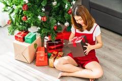 """Νέο χαριτωμένο ασιατικό κορίτσι που κρατά το κόκκινο παρόν κιβώτιο MAS Χ """", χριστουγεννιάτικο δέντρο που διακοσμείται με το καθισ στοκ εικόνες"""