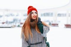 Νέο χαριτωμένο κορίτσι με ένα όμορφο χαμόγελο σε ένα κόκκινο πλεκτό καπέλο και Στοκ Φωτογραφίες