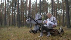 Νέο χαριτωμένο μητρικό γάλα μωρών σίτισης mom στο πάρκο απόθεμα βίντεο
