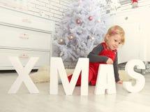 Νέο χαριτωμένο παιδί στα Χριστούγεννα εσωτερικά Στοκ εικόνα με δικαίωμα ελεύθερης χρήσης