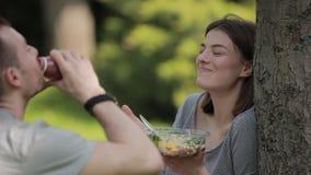 Νέο χορτοφάγο ζεύγος που τρώει τη σαλάτα και που πίνει τη συνεδρίαση καταφερτζήδων στο πάρκο φιλμ μικρού μήκους