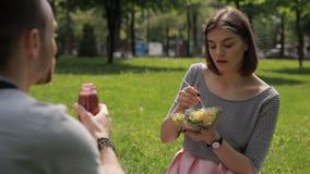Νέο χορτοφάγο ζεύγος που τρώει τη σαλάτα και που πίνει το καταφερτζή σε ένα πάρκο απόθεμα βίντεο
