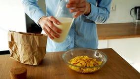 Νέο χύνοντας γάλα γυναικών σε ένα κύπελλο των δημητριακών στην κουζίνα r απόθεμα βίντεο