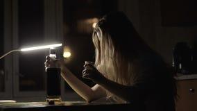 Νέο χύνοντας οινόπνευμα γυναικών στο γυαλί από ένα μπουκάλι και κατανάλωση στο σκοτεινό δωμάτιο απόθεμα βίντεο