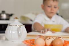 Νέο ψήσιμο αγοριών στην κουζίνα που χρησιμοποιεί τα αυγά Στοκ Εικόνες