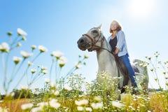Νέο όμορφο άσπρο άλογο ιππασίας γυναικών Στοκ φωτογραφία με δικαίωμα ελεύθερης χρήσης