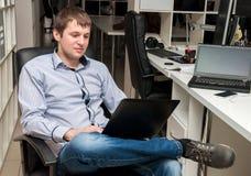Νέο όμορφο άτομο με τον υπολογιστή στο γραφείο στοκ εικόνα με δικαίωμα ελεύθερης χρήσης