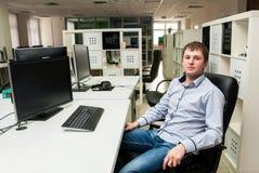 Νέο όμορφο άτομο με τον υπολογιστή στο γραφείο Στοκ Φωτογραφία