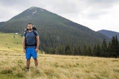 Νέο όμορφο άτομο με το σακίδιο πλάτης που στέκεται στη χλοώδη κοιλάδα βουνών στο διαστημικό υπόβαθρο αντιγράφων αιχμής θερινών τη στοκ εικόνες